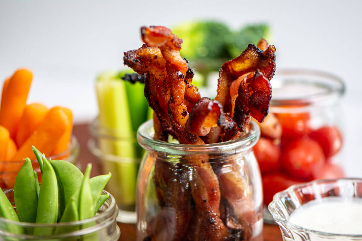 jars with twisted bacon, sugar peas, carrots, celery and tomatoes.